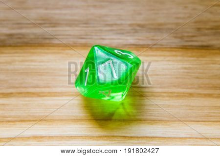 A Translucent Green Ten Sided Playing Dice On A Wooden Background With Number Seven On A Top