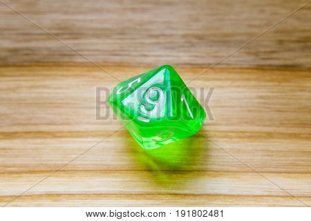 A Translucent Green Ten Sided Playing Dice On A Wooden Background With Number Nine On A Top