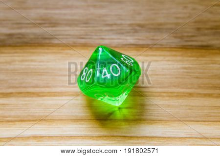 A Translucent Green Ten Sided Playing Dice On A Wooden Background With Number Fourty On A Top