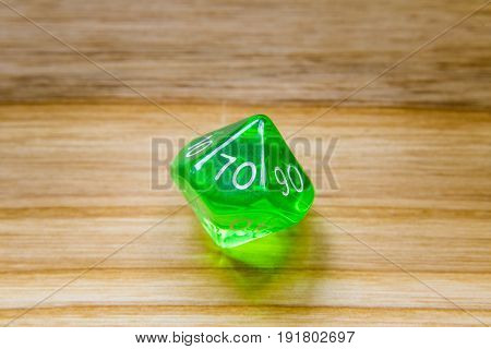 A Translucent Green Ten Sided Playing Dice On A Wooden Background With Number Seventy On A Top