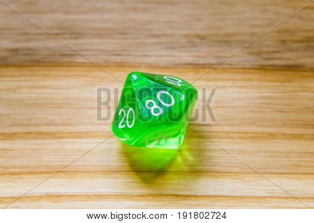 A Translucent Green Ten Sided Playing Dice On A Wooden Background With Number Eighty On A Top