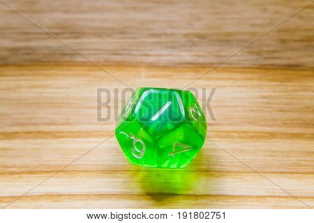 A Translucent Green Twelve Sided Playing Dice On A Wooden Background With Number One On A Top