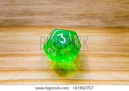 A Translucent Green Twelve Sided Playing Dice On A Wooden Background With Number Three On A Top