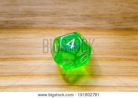 A Translucent Green Twelve Sided Playing Dice On A Wooden Background With Number Four On A Top
