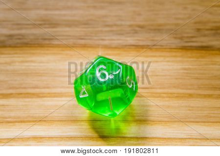 A Translucent Green Twelve Sided Playing Dice On A Wooden Background With Number Six On A Top