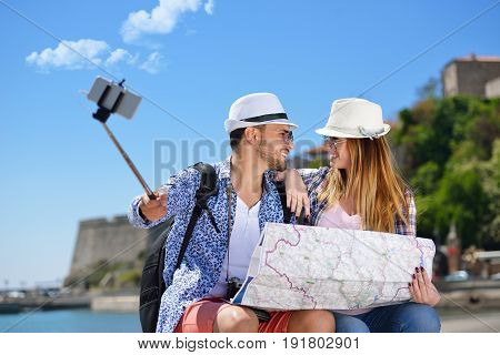 Couple of tourists photographing a selfie in a city street