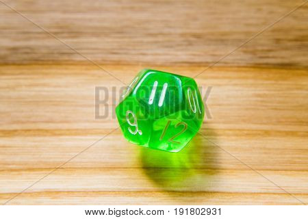 A Translucent Green Twelve Sided Playing Dice On A Wooden Background With Number Eleven On A Top
