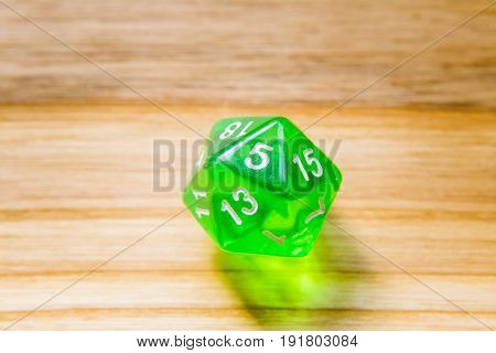 A Translucent Green Twenty Sided Playing Dice On A Wooden Background With Number Five On A Top