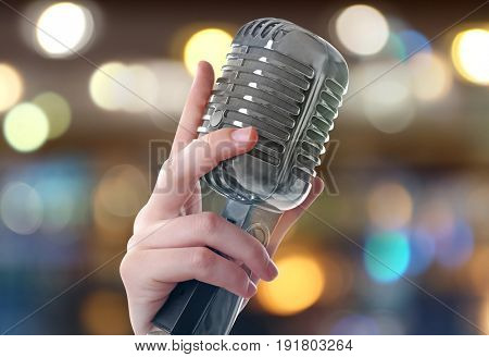 Female hand with vintage microphone on blurred lights background. Concept of Christmas music and songs
