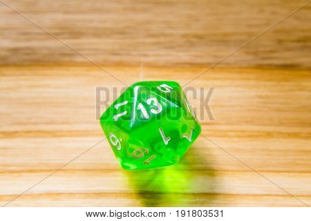 A Translucent Green Twenty Sided Playing Dice On A Wooden Background With Number Thirteen On A Top