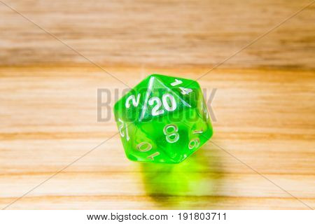 A Translucent Green Twenty Sided Playing Dice On A Wooden Background With Number Twenty On A Top
