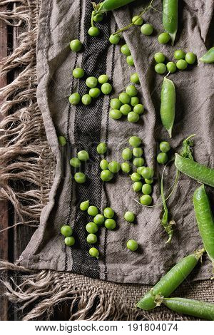 Young organic green pea pods and peas over old dark wooden planks with sackcloth textile background. Top view with space. Harvest, healthy eating.