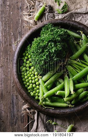 Young organic green pea pods and peas in terracotta tray and bundle of parsley over old dark wooden planks with sackcloth textile background. Top view with space. Harvest, healthy eating.