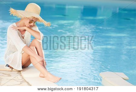Young woman sun bathing in spa resort swiming pool