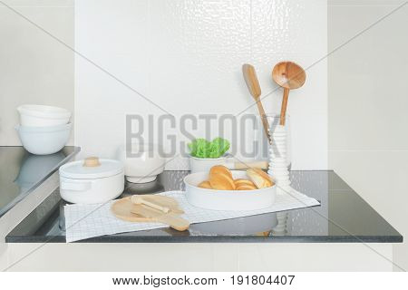 Tray Of Bread  And White Ceramicware On Black Counter Top In The Kitchen
