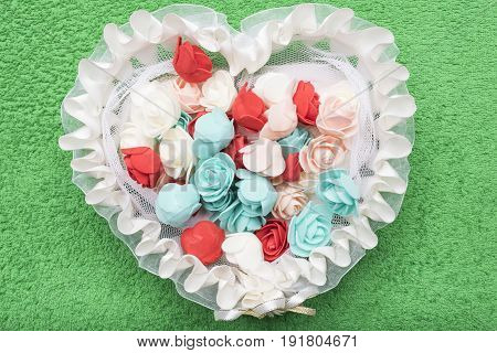 Artificial little white red and turquoise roses lie in a white lace basket in the form of a heart on an emerald green background.
