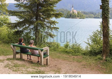 Bled, Slovenia - June 3, 2017: Tourists Sitting On A Bench On The Bank Of Lake Bled. Church Of Backg