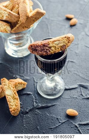 Traditional italian almond cookies cantuccini with glass of red wine on black stone background. Homemade biscotti on dark concrete table.