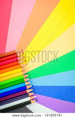 Sharp colorful pencils in a row on colorful paper background
