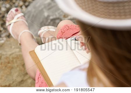 One Pretty European Woman Is Sittin On A Stone C And Writing Some Idea, Letter Or Job By Pen In Her