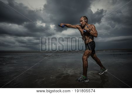 Strong boxer doing boxing exercise at sunset