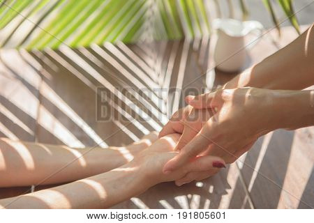 Essential oil in jug pouring on female hands in spa