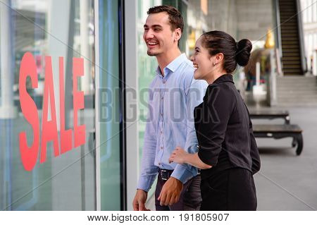 caucasian woman and man excited when see the price tag on sale clothing fashion at the store discount shock price