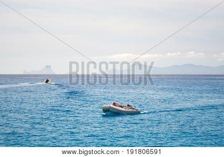 Formentera Spain - June 09 2017: Person relaxing on a inflatable boat at Mediterranean Sea Cala Saona. Formentera. Balearic Islands. Spain