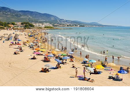 ALCOSSEBRE, SPAIN - JUNE 11, 2017: People enjoying the warm weather at Romana beach in Alcossebre, in the Costa del Azahar, Spain