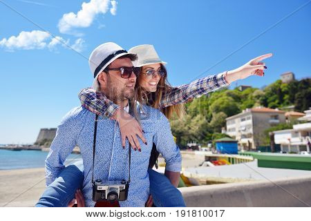 Side view of a couple of 2 tourists with a suitcase sitting relaxing and enjoying vacations in a colorful promenade. Tourism concept.