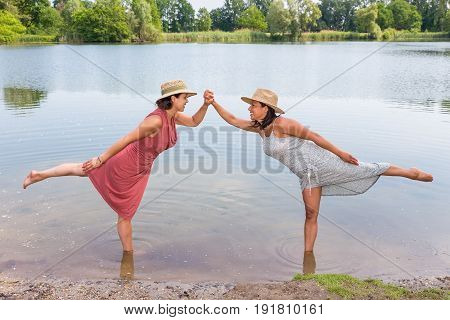 Two friends stand together on one leg in water of lake