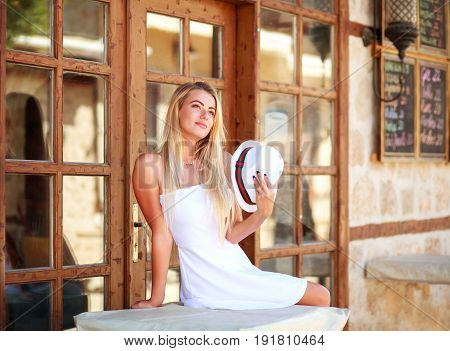 Young dreamy woman relaxing on streets of old tourist town
