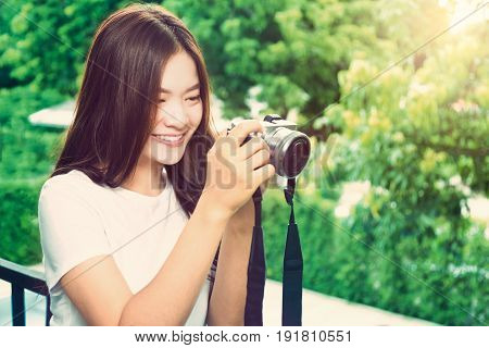 happy young beautiful asian woman smiling and taking picture with her camera blurred trees and warm sun light background vintage color tone