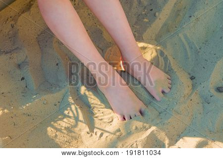 Baby feet buried in the sand at the beach during summer