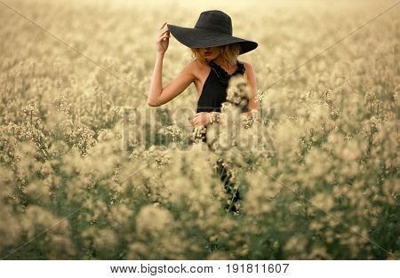Young woman in black dress and hat among flowering meadow. Her face is covered with hat and she looks away.
