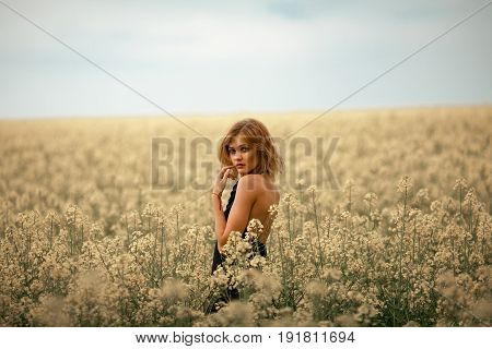 Young woman in black dress among flowering meadow. She turned around and looked at camera.