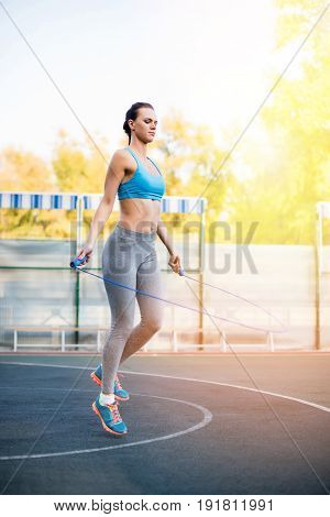 Full Length View Of Young Sportswoman Exercising With Skipping Rope On Stadium