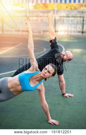 Sporty Couple Doing Side Plank With Raised Hands On The Stadium