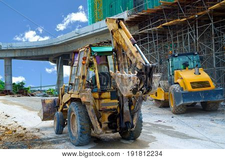 Backhoes standing at highway of construction site