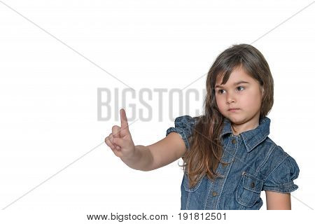 Little girl with a serious expression on her face is pointing index finger into space upwards. All is isolated on the white background.