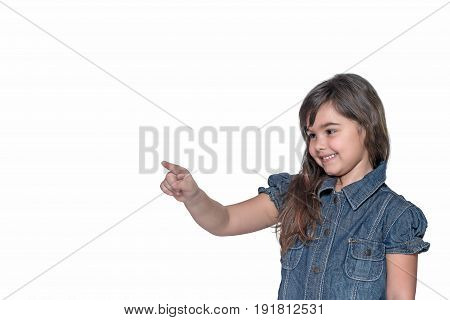 Smiling little girl is pointing her index finger into space. All is isolated on the white background.