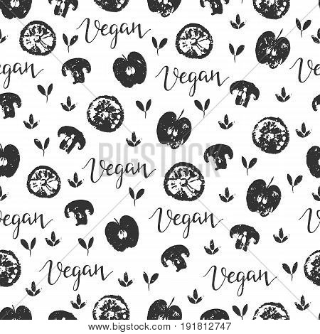 Vector seamless pattern with fruit and vegetables. Apples, lemon, mushrooms and word vegan.  Hand drawn black and white background. Perfect for vegan food menu or surface pattern design.