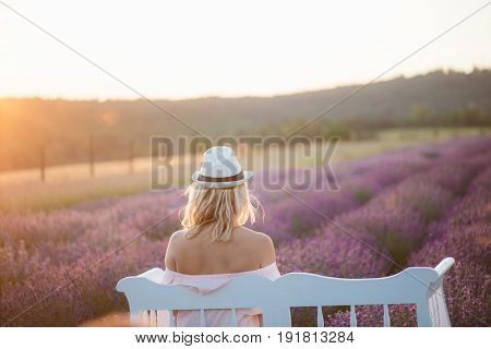 Back view of beautiful long hair woman watching sunset at lavender field on a white vintage bench.
