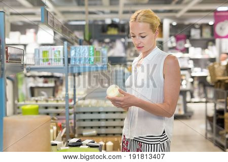 Beautiful young caucasian woman choosing the right item for her apartment in a modern home decor furnishings store. Shopping in retail store.