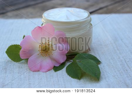 Organic cosmetic cream with rose hip flower