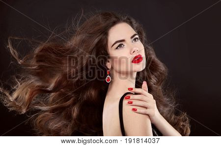 Beauty hair. Red manicure. Brunette girl with makeup and long shiny wavy hair. Fashion earring jewelry. Beautiful model portrait with curly hairstyle, manicured nails over dark background.