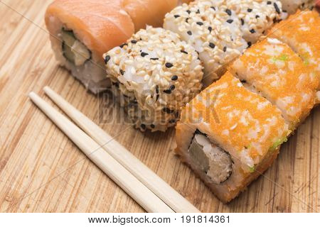 Sushi rolls with salmon red caviar white and black sesame and sushi sticks lie on a light wooden board close-up view