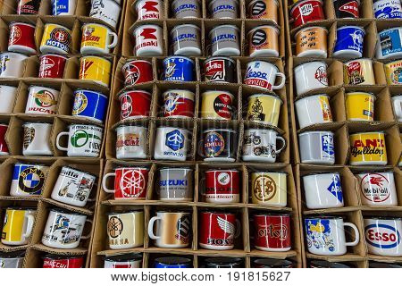 STUTTGART GERMANY - MARCH 03 2017: Souvenir mugs with logos of famous automotive brands oil companies and beverage producers. Europe's greatest classic car exhibition