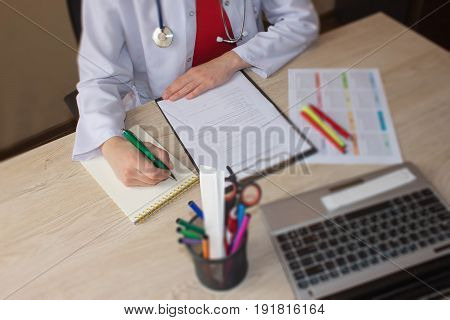 Doctor sits in a medical office in the clinic and writes medical history. Healthcare and medical concept. Medicine doctor's working table