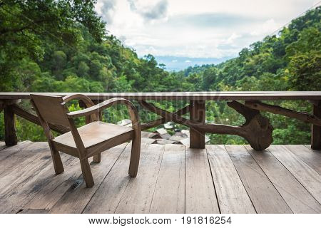 Scenery of wooden armchair on terrace inside rural village surrounded by rainforest in northern region of Thailand.